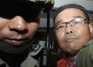 **FILE** in this Oct. 7, 2015, photo, Hong Sok Hour, right, a senator from the opposition Cambodia National Rescue Party, is escorted by riot police officers at Phnom Penh Municipal Court in Phnom Penh, Cambodia. A Cambodian court on Monday, Nov. 7, 2016, sentenced an opposition senator to seven years in prison over comments he posted on Facebook criticizing a 36-year-old border agreement with neighboring Vietnam. (AP Photo/Heng Sinith, FILE)